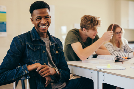 Young african student sitting at table looking at camera and smiling with his classmates studying by. Young university students in classroom. Stok Fotoğraf