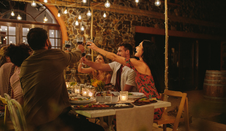 Group of friends making a toast with drinks at party. Young people sitting at a table with food, toasting drinks and enjoying dinner together.