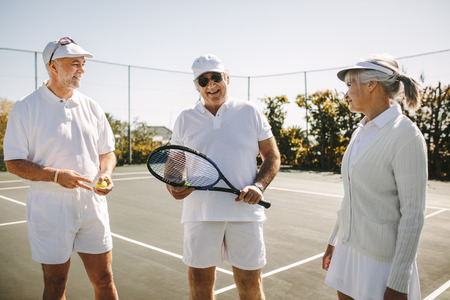Cheerful men in tennis wear talking to a senior woman standing on a tennis court. Smiling old man standing with his playmates holding a tennis racket. Stock Photo