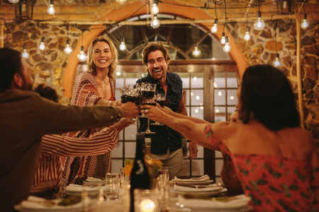 Host couple toasting drinks with guest at dinner party. Young cheerful people celebrating with drinks at party. Banque d'images - 118799649