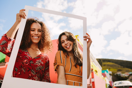 Two smiling woman standing together and holding empty frame outdoors. Beautiful female friends holding a blank picture frame looking at camera, smiling and  sticking out tongue.