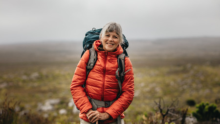 Portrait of a smiling female hiker standing on top of a hill on a winter day. Senior woman wearing jacket and backpack hiking on a hill.