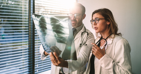 Doctors colleagues look at the x-ray of the patient and discussing over the treatment. Male and female doctors looking at x-ray film and diagnosing patient illness in the hospital.