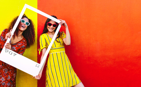 Portret van twee vrouwen die een leeg fotolijstje in de hand houden en glimlachen. Meisjes die zonnebril dragen die zich tegen rood en geel gekleurde muur bevinden. Stockfoto