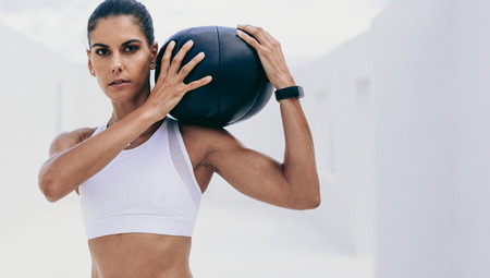 Close up of a fitness woman holding a medicine ball on her shoulder doing workout. Woman in fitness wear doing fitness training using a medicine ball.