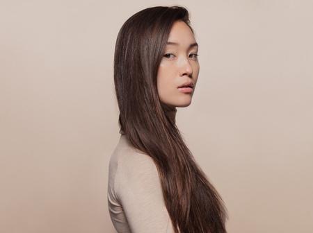 Porträt der schönen jungen Frau mit dem langen braunen Haar, das gegen beige Hintergrund steht. Asiatische Frau mit einem langen glatten Haar, das Kamera betrachtet.