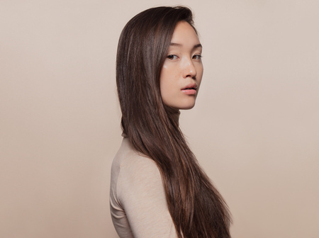 Portrait of beautiful young woman with long brown hair standing against beige background. Asian woman with a long straight hair looking at camera. Reklamní fotografie - 118800437