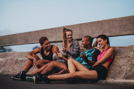 Multi-ethnic friends sitting outdoors on the city street after workout. Fitness group resting and talking after workout.