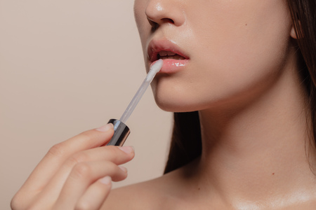 Close up of woman applying lip gloss. Cropped shot of korean girl putting on makeup on her lips against beige background.