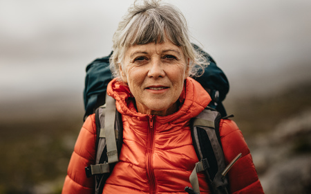 Close up of a senior woman wearing jacket and carrying a backpack. Senior woman on a hiking trip on a winter day.