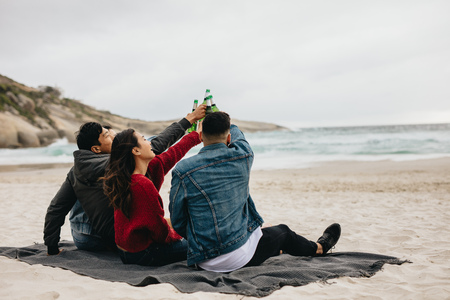 Group of asian friends drinking beer on the beach. People on the beach having a party with drinks.