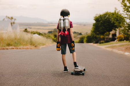 Rear view of young boy with helmet and toy jetpack standing with his skateboard and looking down the road. Jetpack boy with skateboard 스톡 콘텐츠