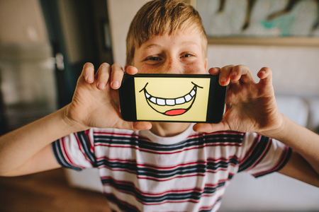 Boy holding a smartphone in front of his face with smiley picture on the display. Boy pretending to be happy at home. Stock Photo