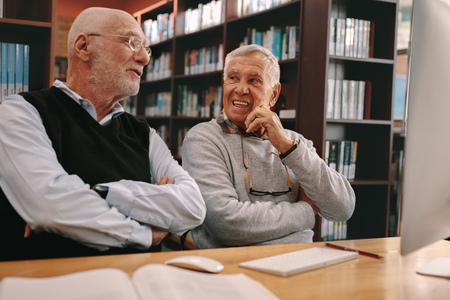 Two senior men sitting in a library and learning with books and a computer on the table. Senior learners discussing sitting in classroom. Stock Photo
