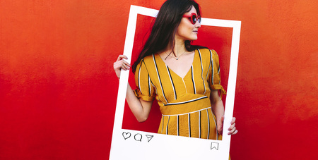 Woman holding a blank social media photo frame in hand and looking away. Female blogger wearing sunglasses standing against red looking through at empty photo frame.