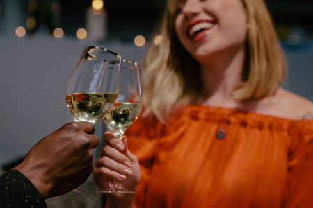 Man and woman toasting on date night. Smiling woman toasting glass of wines with her boyfriend.
