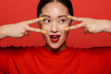 Close up portrait of young asian woman with beautiful make up looking through fingers on red background.
