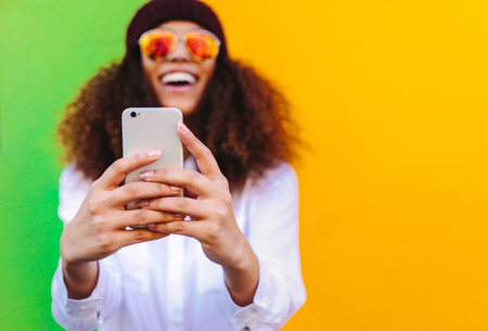 Curly haired african girl taking a selfie using smartphone. Focus on mobile phone in hand of woman taking selfie on yellow and green background. 免版税图像