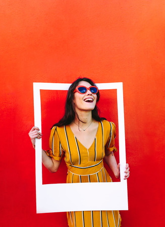 Stylish woman standing against the red wall and holding a large photo frame. Beautiful girl wearing sunglasses looking through blank picture frame.