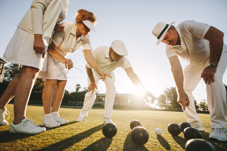 Cropped shot of a group of friends playing boules in a park with sun in the background. Senior men and women talking about position of boules pointing at the boules on the ground. Stock Photo
