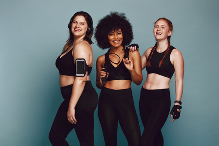 Portrait of mixed race women standing together against grey background and laughing. Diverse group women in sportswear.