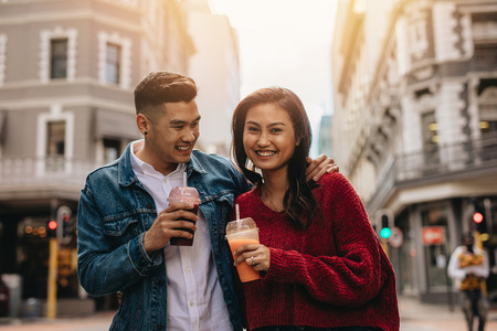 Young asian couple walking on the city street with fresh juice. Happy young man and woman on city street with juice.