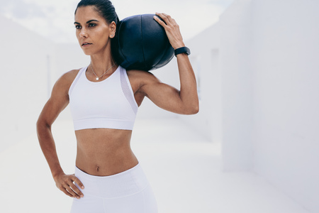 Athletic woman doing fitness workout holding a medicine ball on her shoulder. Woman in fitness wear doing fitness training.