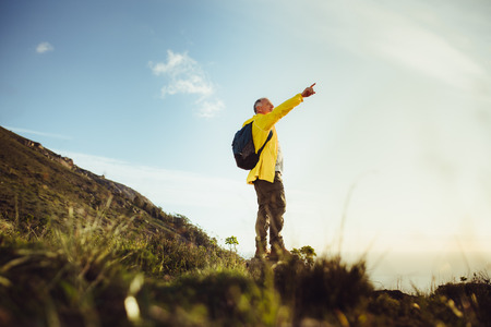 Senior man standing on a hill wearing a backpack and pointing at the sky. Adventure seeking man standing on top of a hill looking away.