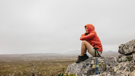 Woman sitting on a rock on a hilltop looking at the beauty of nature. Senior woman sitting relaxed after her trek with a hiking pole by her side.