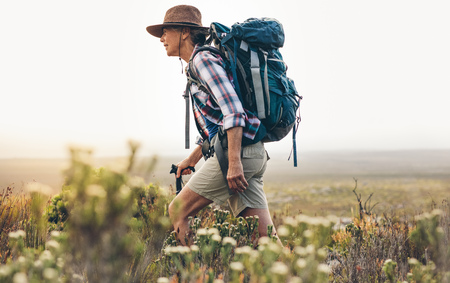 Side view of a senior woman trekking in the wild. Woman wearing backpack and hat walking through bushes and plants during trekking holding a hiking pole. Stock fotó - 118814443