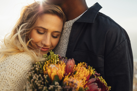 Young woman hugging her boyfriend with flowers. Woman embracing her man with love.