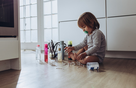 Kid sitting on floor at home playing with ear buds and cosmetics. Kid playing with household articles sitting alone at home. 写真素材