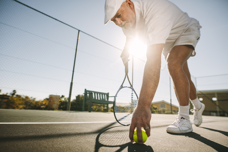 Close up of a senior man bending down to pick a tennis ball with sun in the background. Senior man playing tennis on a sunny day.