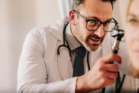 Médecin ORL expérimenté examinant l'oreille du patient avec un otoscope. Médecin de sexe masculin examinant l'oreille du patient avec un instrument dans sa clinique. Banque d'images