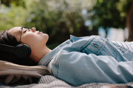 Side view of a woman relaxing outdoors listening to music wearing headphones. Close up of a young woman sleeping outdoors in a park enjoying the mild sun and relaxing. Stock Photo
