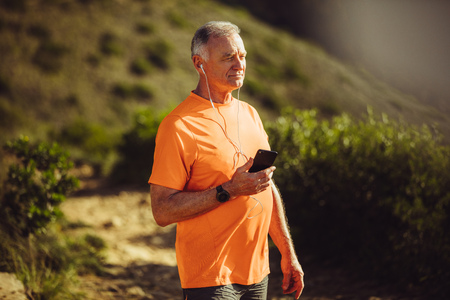 Senior man in fitness wear listening to music on mobile phone during a walk. Portrait of a senior fitness man walking on a hilly trail track listening to music.