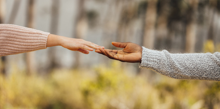 Multi-ethnic couple hands reaching and touching outdoors. Couple approaching to each other. Female and male hands touching each other by fingers.