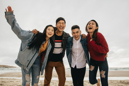 Group of asian friends on the seashore. Young people having great time together at the beach.