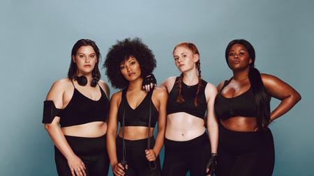 Ritratto di donne di razza mista in piedi insieme su sfondo grigio. Gruppo di donne con diverse dimensioni in abbigliamento sportivo.