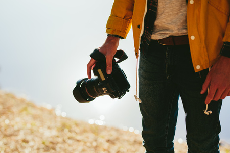 Cropped shot of a man standing outdoors holding a digital camera in hand. Close up of mid section of a man holding a dslr camera.