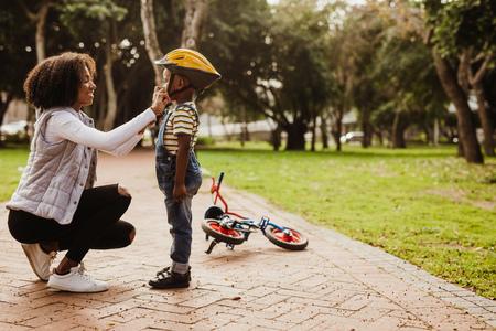 Madre ayudando a su hijo con casco para andar en bicicleta en el parque. Niño preparándose usando casco de bicicleta para comenzar a andar en bicicleta.