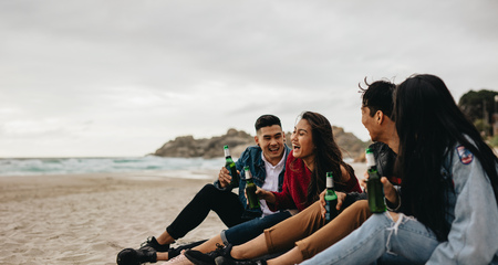 Group of asian men and women sitting at the sea shore with beers. Four young friends partying on the beach.
