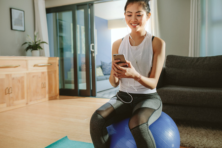 Woman listening to the music while sitting on a exercise ball at home. Happy sporty girl with smartphone relaxing on a fitness ball. Фото со стока