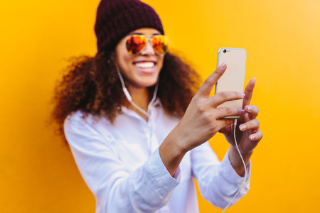 African girl taking a selfie using mobile phone. Focus on mobile phone in hand of female taking selfie on yellow background.