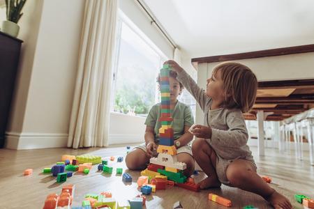 Kinder bauen einen Turm mit Bausteinen. Glückliche Kinder, die mit Spielzeug spielen, das zu Hause auf dem Boden sitzt.