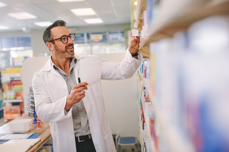 Mature chemist with a prescription searching right medicine on shelves in pharmacy. Male pharmacist holding prescription checking medicine in pharmacy.