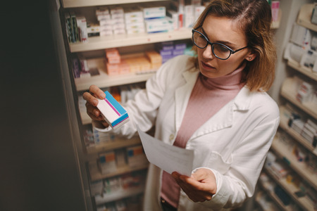Chemist with a prescription searching right medicine on shelves in pharmacy. Female pharmacist holding prescription checking medicine in pharmacy.