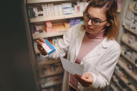 Químico con receta buscando el medicamento adecuado en los estantes de la farmacia. Farmacéutico de sexo femenino que sostiene la prescripción que controla la medicina en farmacia