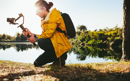 Man using advanced technology gadgets to shoot photos of nature. Traveler sitting beside a lake taking a photo on a dslr camera mounted on a hand held gyroscope gimbal. Stock Photo
