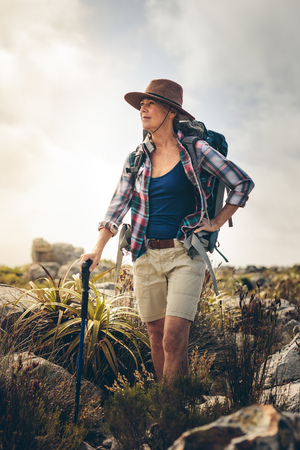 Senior woman on a hiking trip standing on a hill and looking away. Woman wearing hat and backpack trekking a rocky path holding a hiking pole. Stockfoto